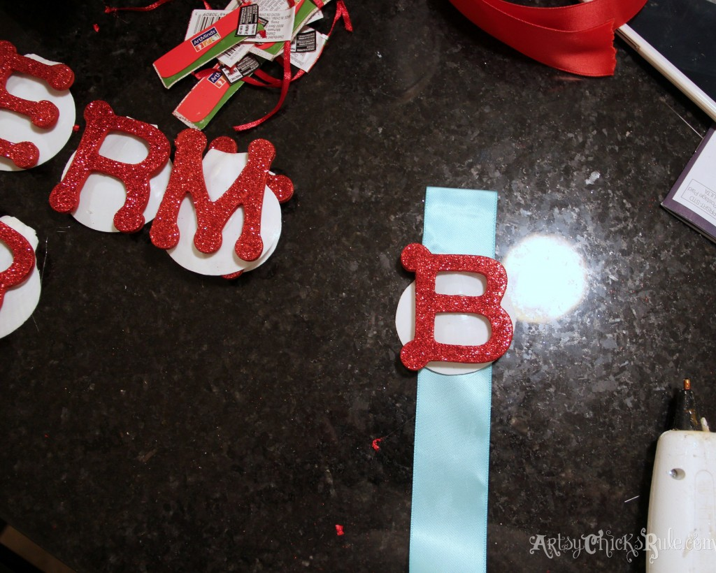 Hot glue letter to shell, shell to ribbon